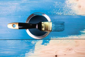 Painting in a blue color. Paint can with brush