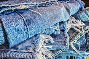 An abstract pile of several different pairs of old, used, ragged, worn and torn blue jeans ready to be recycled.