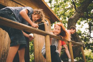 Friends who are children working together to build a treehouse, hammering, helping and sawing on a summer day